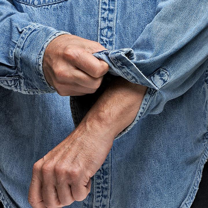 man-in-denim-shirt-rolling-up-his-sleeves-PDMGUZJ